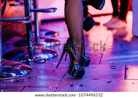 legs of a female dancer in high heeled shoes and tights in a net behind the bar counter #1074496532