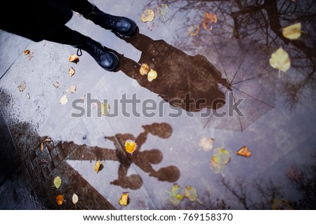 Stock Photo Legs of a girl in black shoes in a puddle after a rain. Autumn in the city. Wet, cold weather. Reflection of the sky in the water. Transparent umbrella.