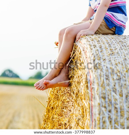 Legs of a kid traditional German bavarian clothes, leather shorts and check shirt. Child sitting on hay stack or bale and dreaming. Active outdoors leisure with children on warm summer day.