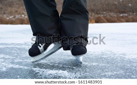 Legs of a man in men's skates on the ice of a wild river. Winter outdoor recreation in the countryside.