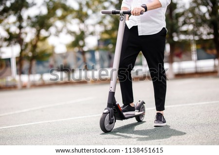 Legs of a man in stylish outfit stand on electric scooter on the street
