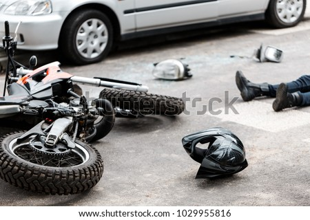 Legs of a person lying on the road after a motorcycle and car accident
