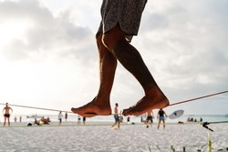 legs of a stranger performing slackline on a tight, tensioned tightrope between two palm trees in the middle of the beach overlooking the sea, sport concept