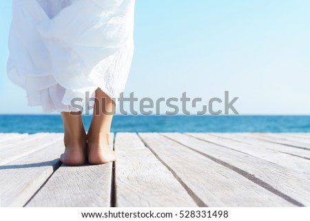 Legs of a woman in white dress on a wooden pier on summer.  Sea and sky background. Vacation, traveling and freedom concept.  #528331498
