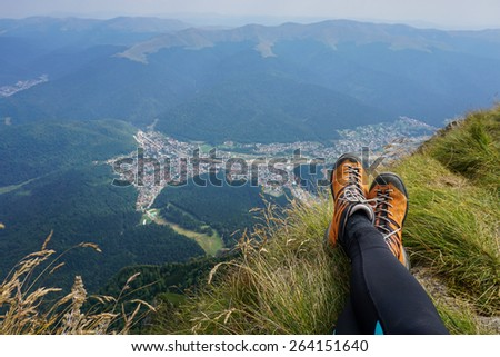 Legs of a woman sitting on the edge n the beautiful mountains of Romania