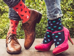 Legs of a young couple in stylish shoes, bright, colorful socks on the wooden terrace on the background of green trees. Lifestyle, fashion, beauty, fun