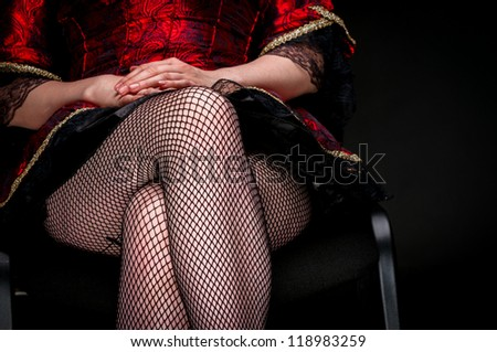 Legs of a young woman against dark background closeup