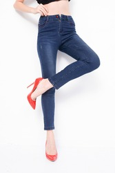 Legs of a young woman in blue jeans and red shoes posing on white background, space for text
