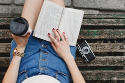 Legs of a young woman in jeans shorts, on a bench in the park. Girl reading a book in a park outdoors with cup of coffee and camera. Close-up. Point of view