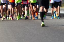 Legs of athletes running half marathon on the road