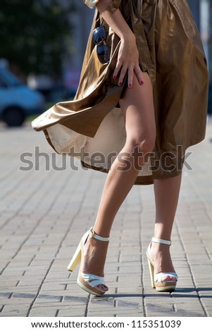 Legs of beautiful girl in high heels in autumn city