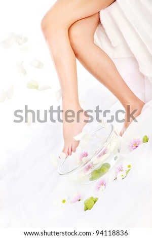 Legs of beautiful girl with aromatherapy bowl and falling petals