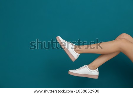 Legs of beautiful woman in stylish shoes on color background #1058852900