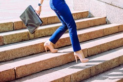 legs of businesswoman go down the stairs with brief case Fast move Business lady. Shadows on stairway.Girl walk on high heels against stoned stairs. Summer sunny day Outdoor. no face