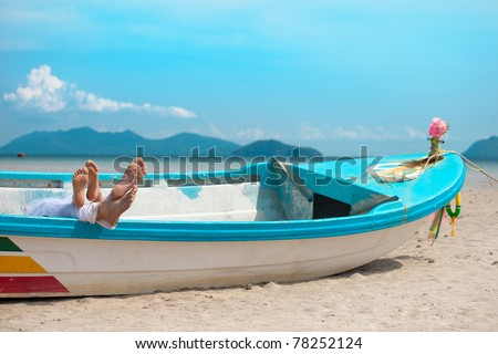 legs of couple in the boat on the beach