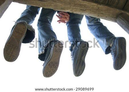 Legs of Couple sitting on the wooden bench