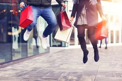 Legs of couple with shopping bags after shopping in city