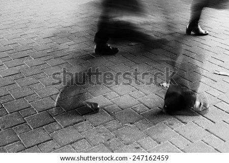 Legs of different people walking on the sidewalk tile on the street. Minsk, Belarus, black and white image. Motion Blur #247162459