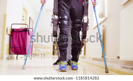 Legs of disable man in the robotic exoskeleton walking through the corridor of the rehabilitation clinic. Doctor helping him.
