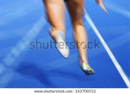 Legs of female runner blurred on blue race track