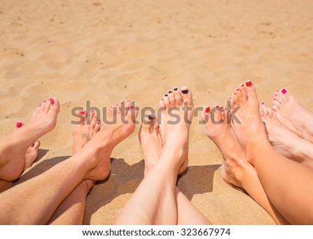 Legs of five girls on the beach
