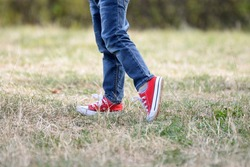 Legs of little boy in red sneakers on the grass. Child feet in red sneakers