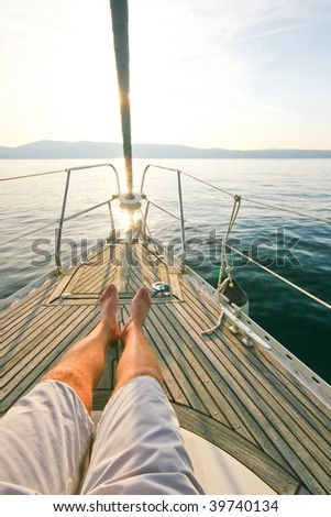 Legs of man lying on a sailboat deck - stock photo