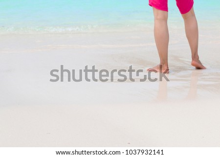 Legs of man wear red shorts standing on the beach. #1037932141