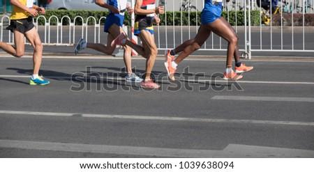 Legs of marathon runners running on city road
