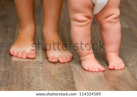 Legs of mother and baby. First steps.