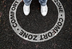legs of person standing in circular marking on road with text COMFORT ZONE, being in or leaving own comfort zone concept