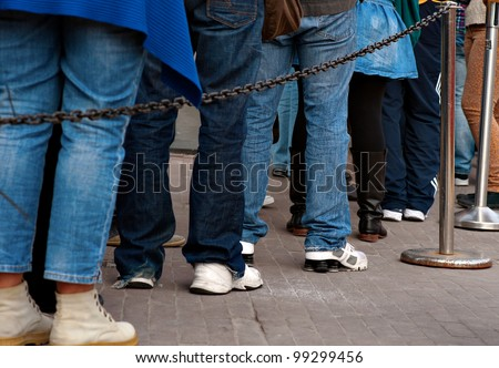 Legs of persons in casual dresses in queue