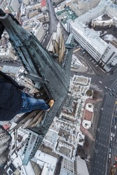 Legs of roofer on big star of Stalin skysraper in Red Gate Square in Moscow at winter