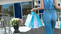 Legs of shopper asian woman holding shopping bags at outdoor outlet area on day in blue color theme. Banner size background with copy space.