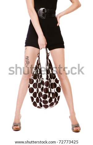 Legs of slim stylish woman with polka dot bag, on white background - stock photo