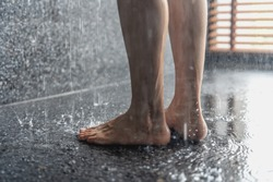 Legs of the girl standing under the shower under the stream of water, health beauty and hygiene concept.