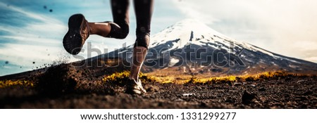 Legs of the woman running on the trail with volcano on the background