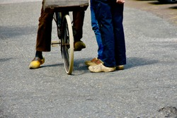 Legs of three Dutch farmers talking in the street on wooden shoes and a bike.