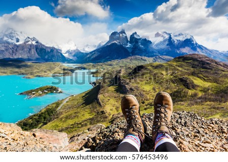Legs of traveler sitting on a high mountain top in travel. Freedom concept. Patagonia, Chile