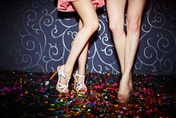 Legs of two girls dancing in night club