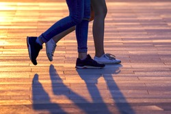 legs of two people walking on the background of sunlight. friendship and synchronization in relationships