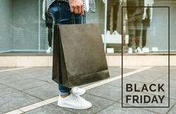 Legs of unrecognizable young man shopping with paper bags in his hand. Black friday concept