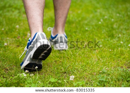 legs of walking man on grass