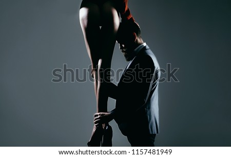 Legs of woman in shoes at man with beard. Woman dominates the man, sex games, obeys man. Dominating in the foreplay sexual game. Luxury ass, huge butt, sexual forms. Love and relations, dominating.