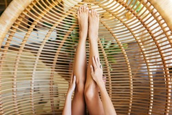 legs of woman in the rattan lounge hanging chair at the balcony with green nature tropical background.