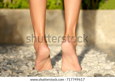 Legs of women walk on a rock and exercise. Foot massage with spa stones in the morning. #717749617