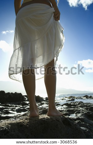Legs of young adult Asian Filipino female standing on rocky beach in Maui Hawaii.
