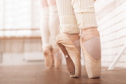 Legs of young ballerinas. They rehearse in the ballet class. They are dressed in white pantyhose and ballet shoes.  Pointe shoes concept.