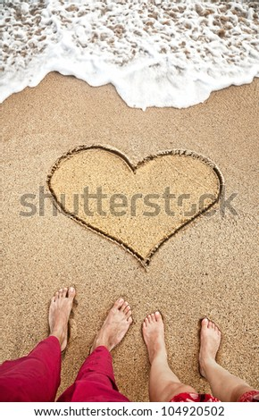 Legs of young couple standing on the beach near heart on the sand with ocean near by