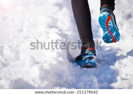 Legs of young sportsman jogging outside in a winter park